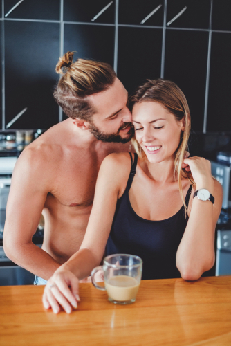 shirtless man kissing woman in kitchen with coffee