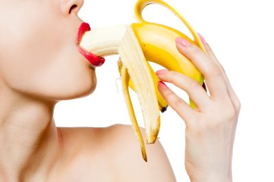 woman sucking on banana to symbolize blow job, oral sex