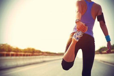 fit woman stretching legs before running