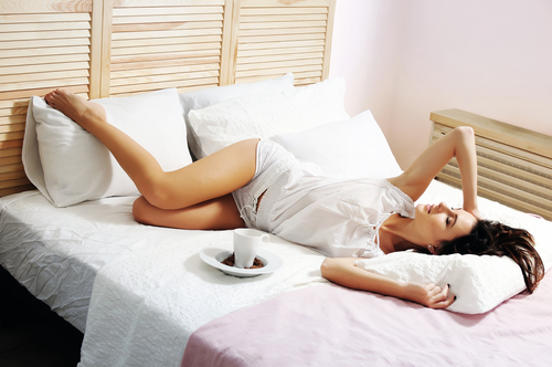 woman lying in bed beside a cup of coffee