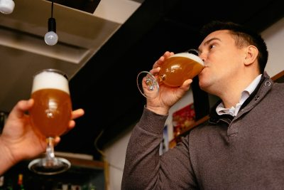 man chugging beer in a bar
