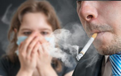 woman covering mouth and nose avoiding second hand smoke
