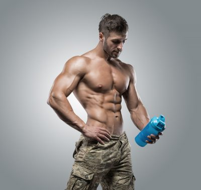 muscular and fit man holding water bottle with protein