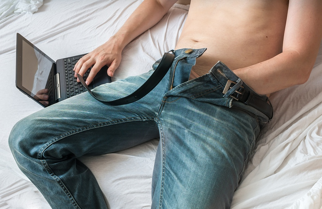 man watching porn with hand inside jeans, masturbating