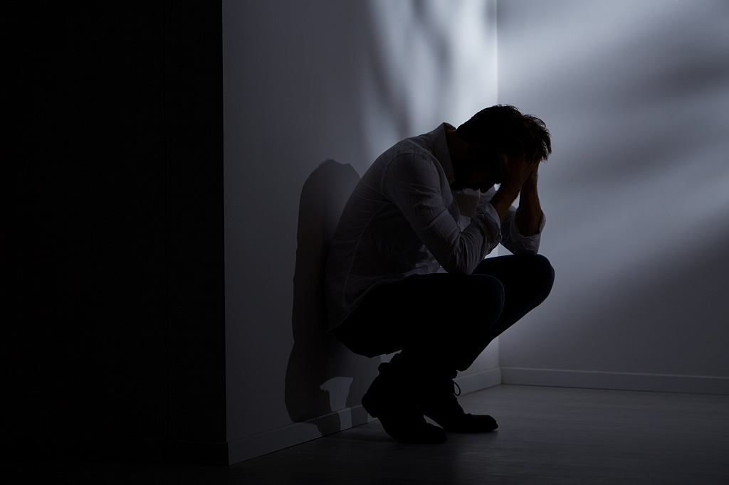 depressed man hunched against the wall holding head in the dark