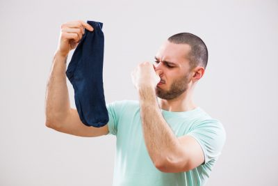 man holding out smelly socks and pinching nose