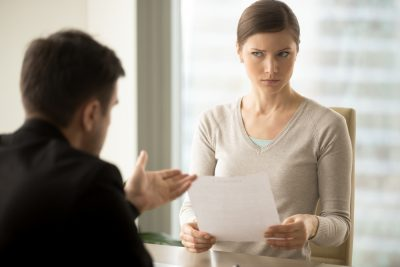 woman looking annoyed at colleague during meeting