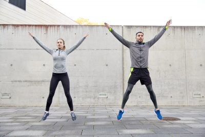couple doing jumping jacks in the morning